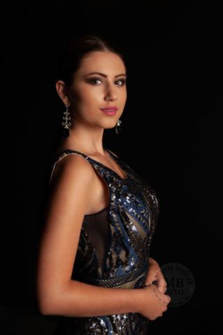 portret zeny dievcata v modrich elegantnich satach na ciernom pozadi s elegantnimi nausnicami