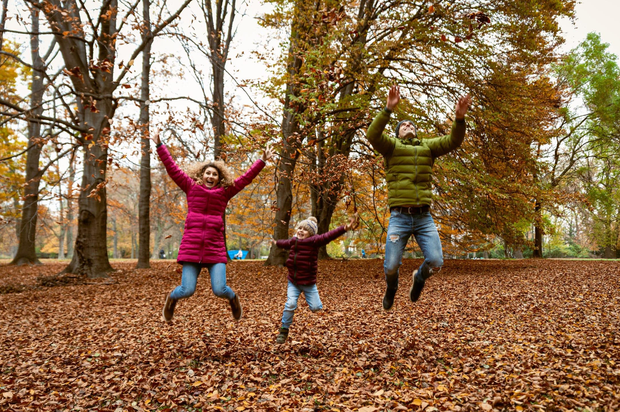 jesenna rodinna fotka vo vyskoku v parku pocas jesene