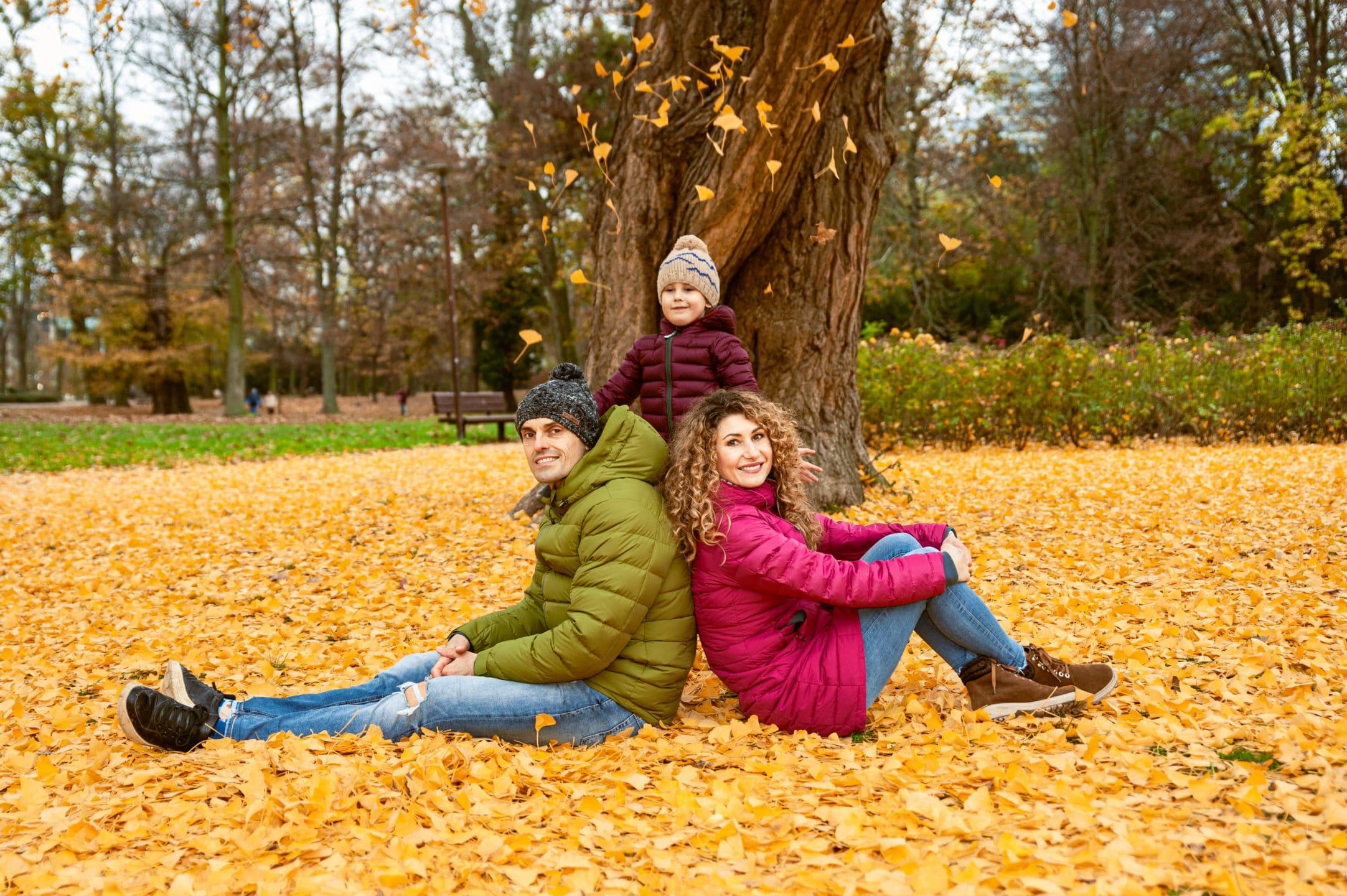 fotka rodinny sediacej v jesennom listi zo synom ktory vyhadzuje listie do vzduchu