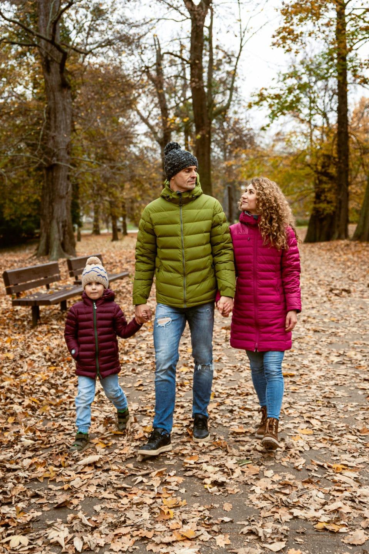 rodinna fotka na jesen kde sa prechadza rodina v parku v jesennom listy a maju zamylivane pohlady