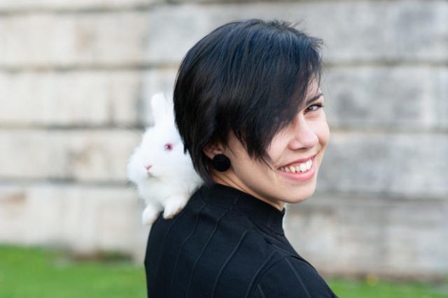 fotka dievcata s bielim zajacom na ramene v mestkom parku