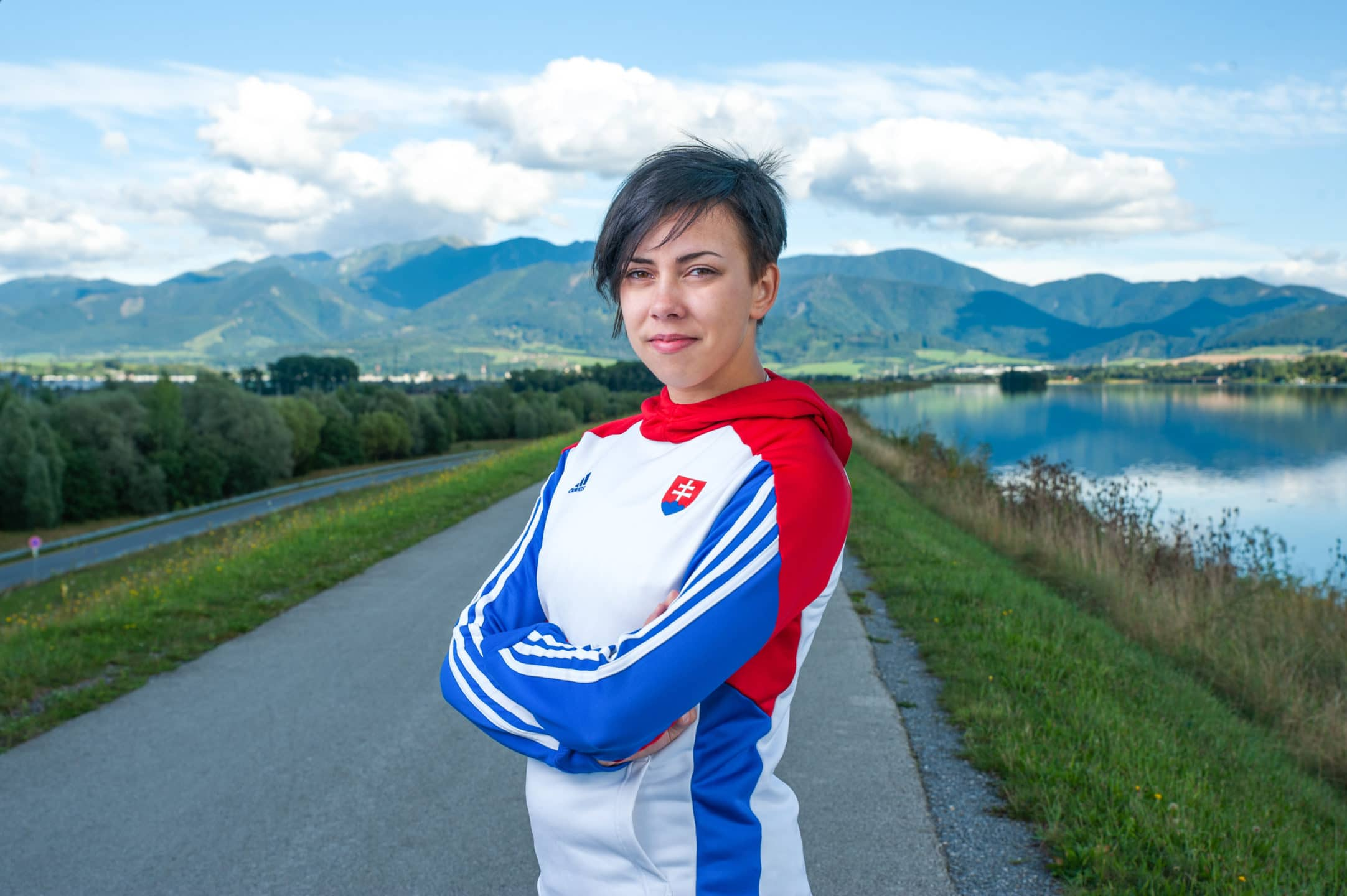 reprezentantka slovenska pozuje na hradzi pri rieke v pozady krajina