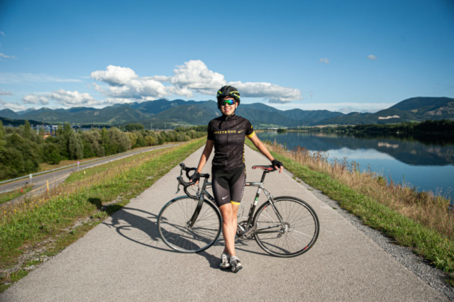 panorama s cyklistkou v cyklodrese nike na cestnom bicykli pri vode a ceste