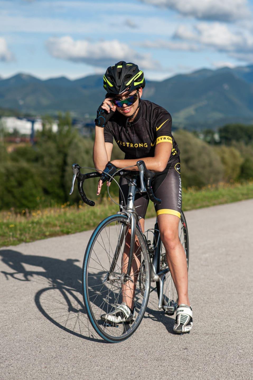 fotka sportovkyne na bicykli v slnecnych okuliaroch na cyklotrase v pozadi lesy a kopce